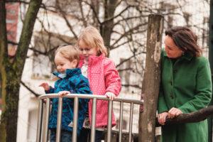 Zwei Kinder, davon eines mit Behinderung, sind auf einem Klettergerüst. Die Mutter steht an der Seite und schaut zu.