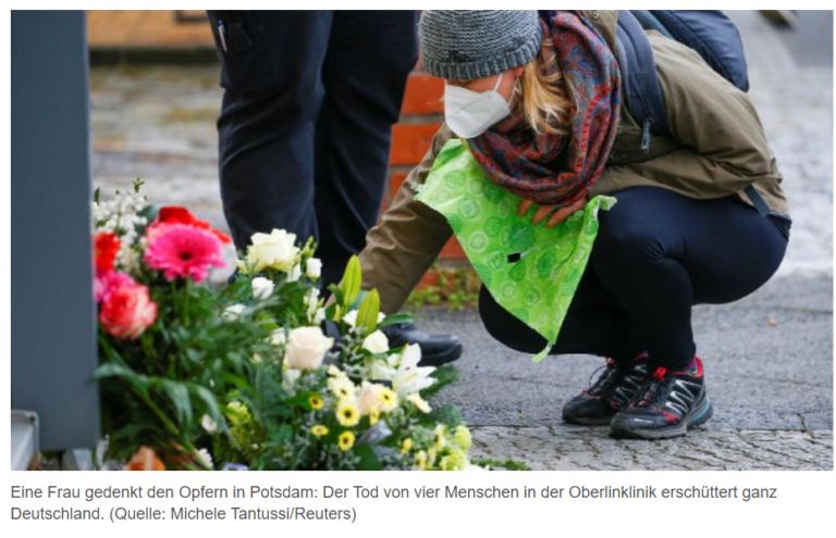 Eine Frau legt an einer Gedenkstätte Blumen nieder