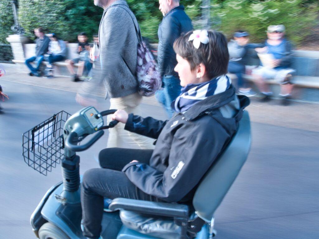 Karina, eine Frau mit kurzen, braunen Haaren und einer roten Blume im Haar, sitzt in einem elektronischen Scooter. Sie trägt eine schwarze Jacke und Hose und ein blau-weiß gestreiftes Halstuch über ihrer Halskrause. Im Hintergrund sitzen mehrere Menschen auf einer Bank und zwei Männer gehen neben Karina auf einer schmalen Straße.