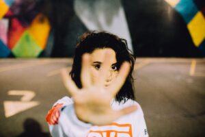Eine weiße Frau mit schwarzen Haaren streckt ihre Hand zur Kamera aus, so das ihr Gesicht nihct zu sehen ist.