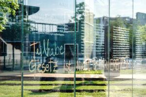 An einer Glasfassade steht mit Filsstif der Text: Teilhabegesetz ist nicht barrierefrei
