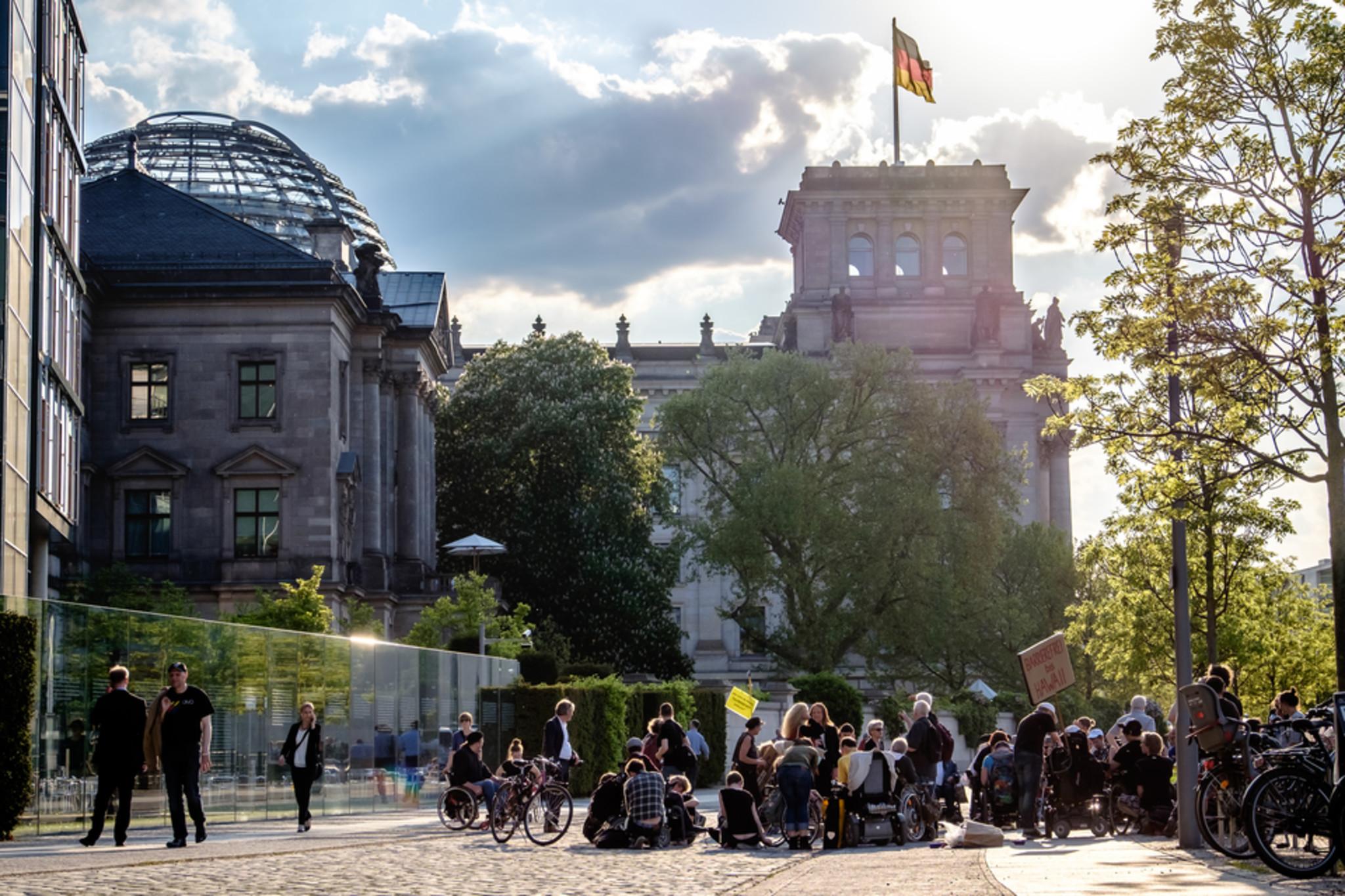 Blick auf den Reichstag in Berlin bei Sonnenschein. Davor stehen mehrere Menschen und demonstrieren.
