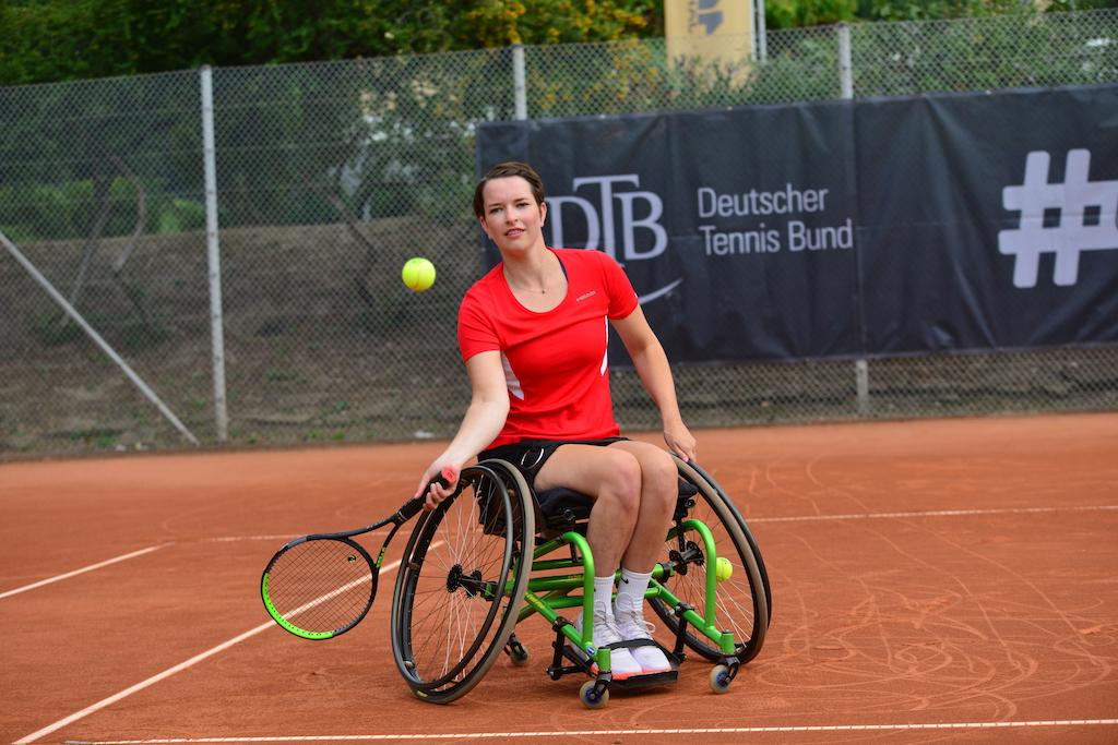 Foto von Britta Wend. Sie sitzt in einem Sportrollstuhl auf einem Tennisplatz, trägt ein rotes T-Shirt und schlägt einen Ball.