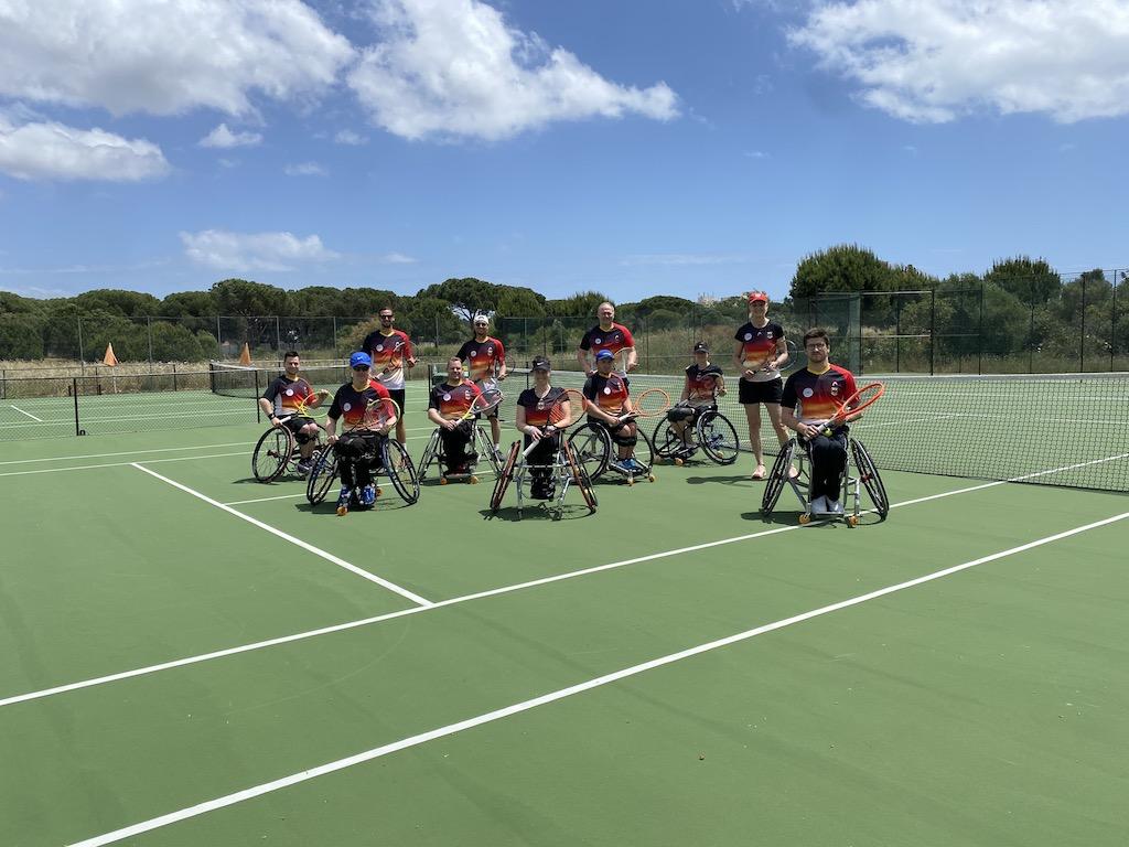 Foto der Deutschen Rollstuhltennis Nationalmannschaft. Mehrere Personen sitzen in Rollstühlen nebeneinander und halten Tennisschläger in der Hand. Das Foto wurde auf einem Tennisplatz draußen aufgenommen, die Sonne scheint und der Huimmel ist blau.