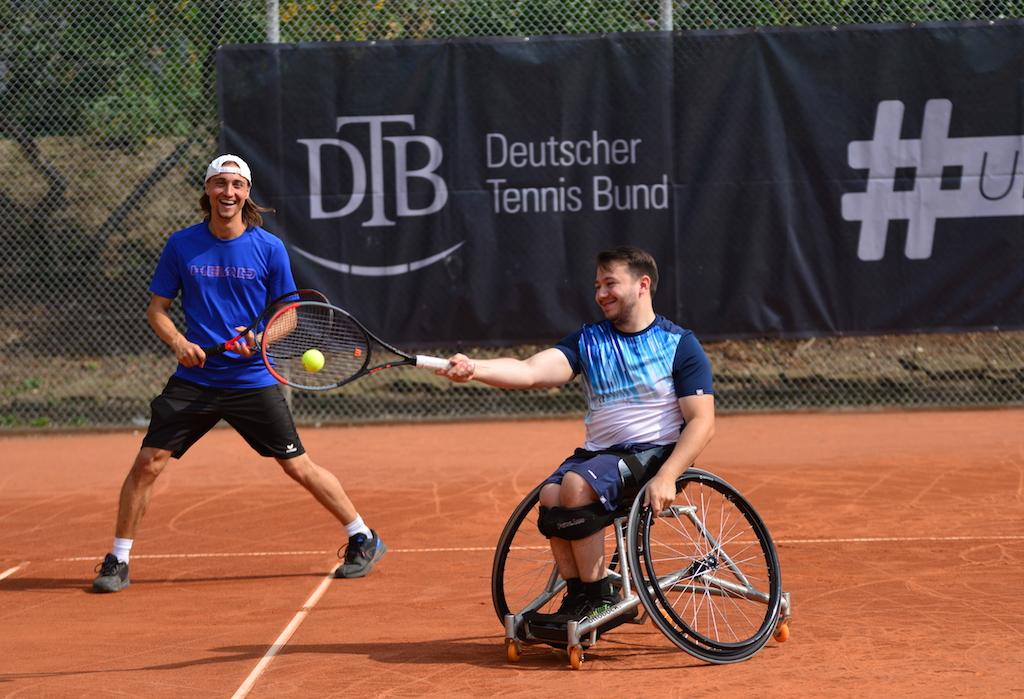Zwei Männer, einer davon im Rollstuhl, spielen gemeinsam Tennis.