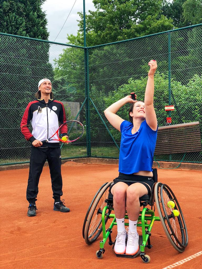 Britta sitzt im Rollstuhl und macht einen Aufschlag beim Tennis. Niklas steht hinter ihr und beobachtet sie.