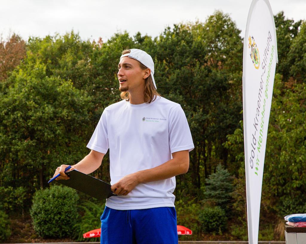Foto von Niklas Höfken auf einem Tennisplatz. Er hat kinnlange Haare, trägt blaue Shorts, ein weißes T-Shirt und eine weiße umgedrehte Base-Cap und hat einen Tennisschläger in der Hand.