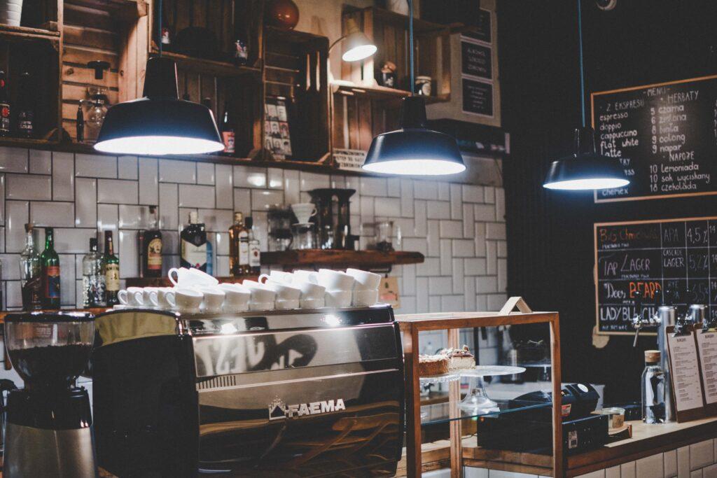 Eine Theke eines Cafés mit Siebträgermaschine mit gemütlicher Beleuchtung. Daneben steht in einer mit Holz umrahmten Vitrine Kuchen.