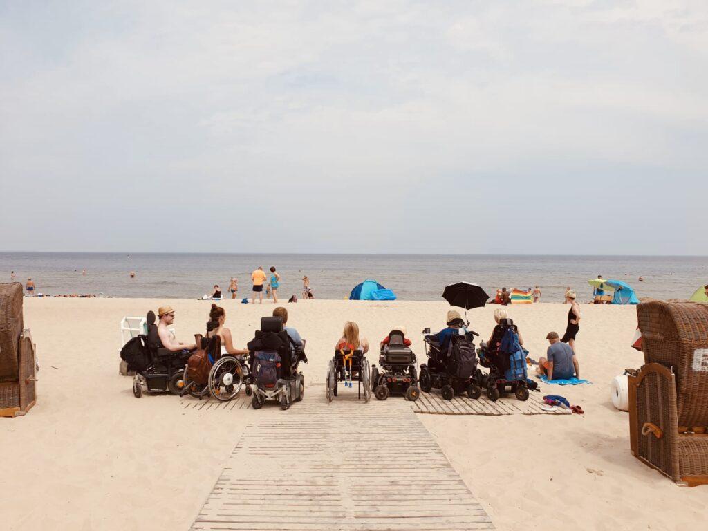 Sieben Personen im Rollstuhl sind am Strand auf einem Holzweg und blicken auf das Meer.
