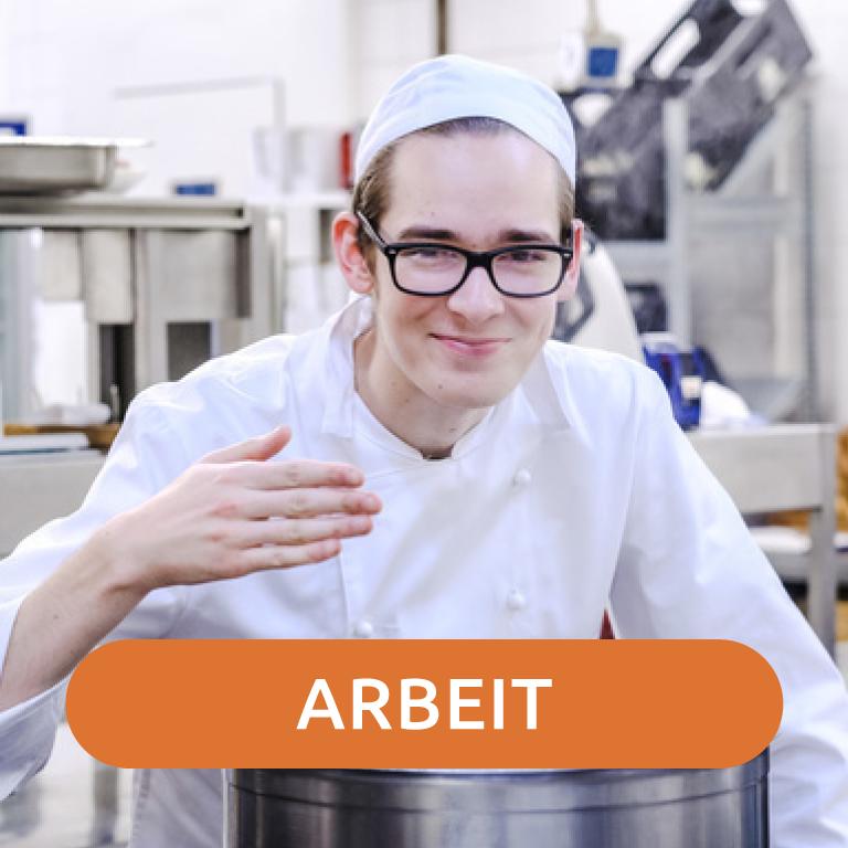 Ein weißer Mann mit lernschwierigkeiten steht in einer Küche und schmeckt Essen ab. Er trägt eine weiße Kochschürze und eine weiße Kochmütze.