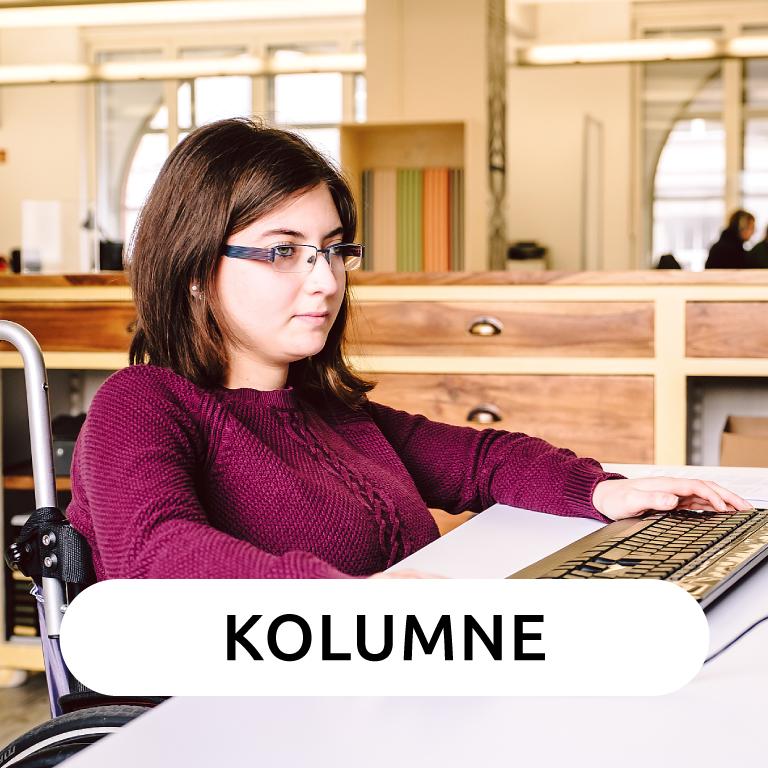 Eine weiße Frau mit schwarzen langen Haaren sitzt im Rollstuhl an einem Tisch und tippt etwas in einen Laptop.