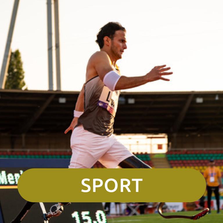 Ein Sportler mit Beiprothesen läuft in einem Stadion.