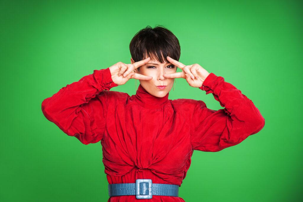 Foto von Francine Jordi. Sieht hat kurze schwarze Haare, trägt einen roten zweiteiler mit großen schwarzen Gürtel und steht vor einer grünen Leinwand. Sie hält ihre Hände vors Gesicht und schaut zwischen die gespreitzten Zeige und Mittelfinger durch.