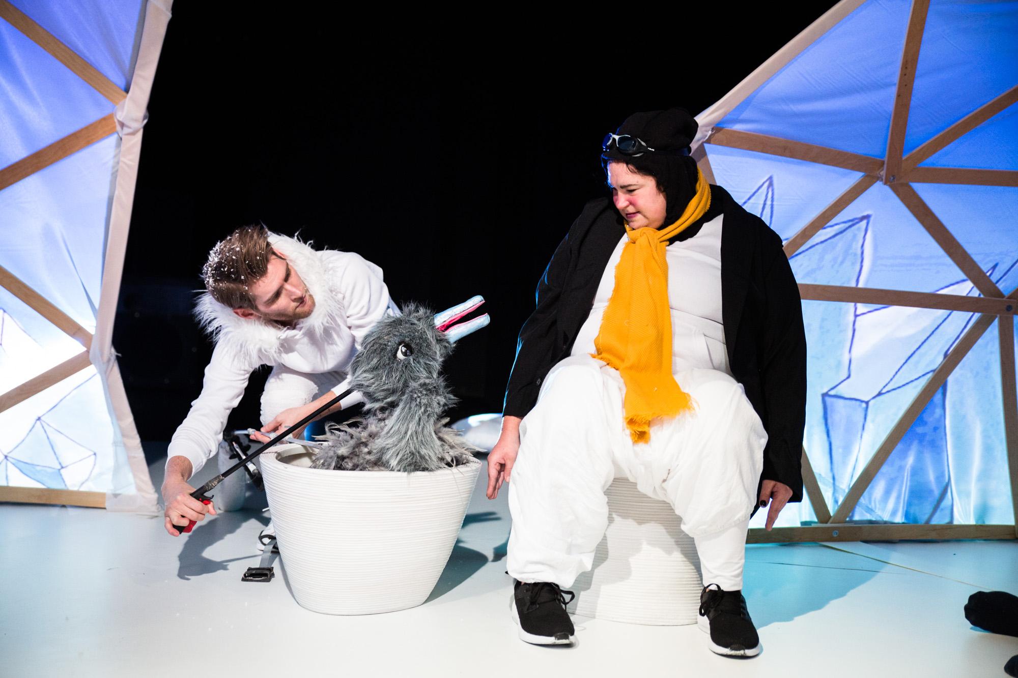 Zwei Personen auf einer Theaterbühne. Der Mann steuert eine Vogelpuppe. Sie zeigt in Richtung einer Frau, die ein Pinguinkostüm trägt.