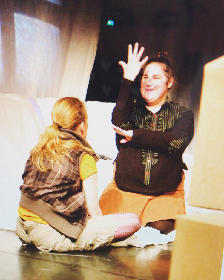 Zwei Frauen auf einer Theatherbühne. Die eine sitzt im Schneidersitz und schaut die andere an, die knieend eine Hand nach oben streckt.