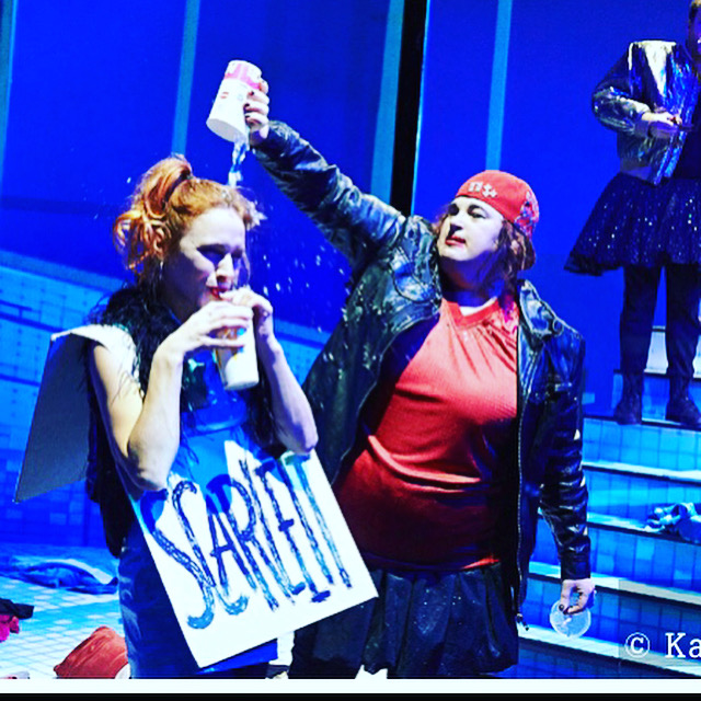 Zwei Frauen auf der Theaterbühne. Die eine schüschüttet der anderen einen Becher wasser über den Kopf.