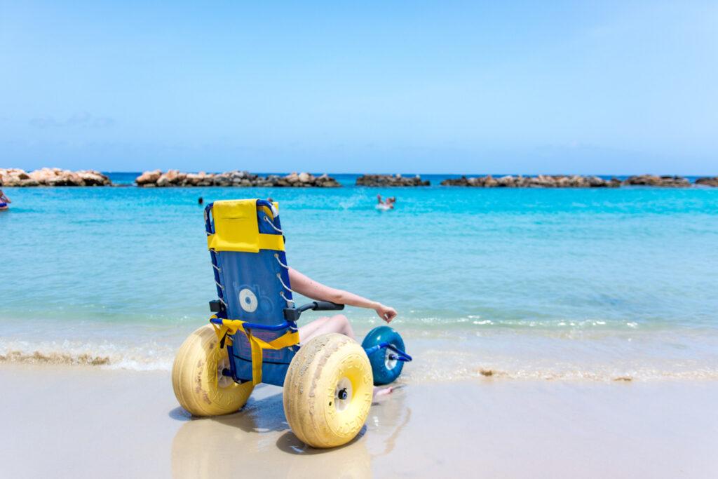 Eine Person sitzt in einem Speziellen Strand-Rollstuhl und blickt auf das kristallklare blaue Meer.