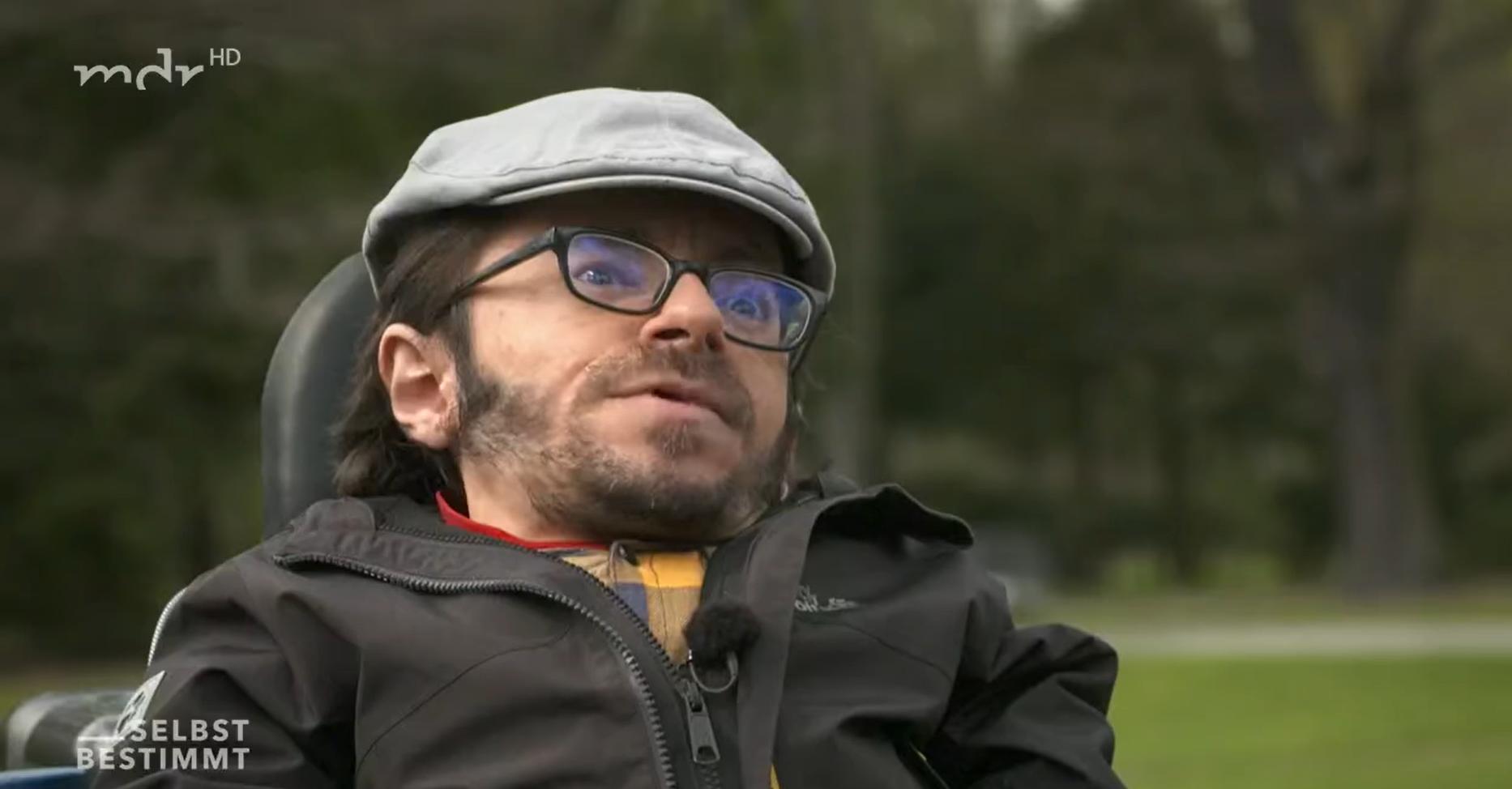 Screenshot aus der Sendung mdr Selbstbestimmt. Raul steht mit seinem Rollstuhl draussen, trägt eine graue Mütze, eine Brille und ein gelb-grau Karriertes Hemd.