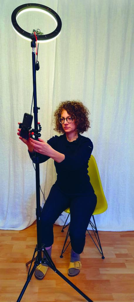 Eine Frau mit schwarzen Klamotten und braunen lockigen Haaren steht in einem Raum vor einer weißen Wand und filmt sich mit dem Smartphone selbst.
