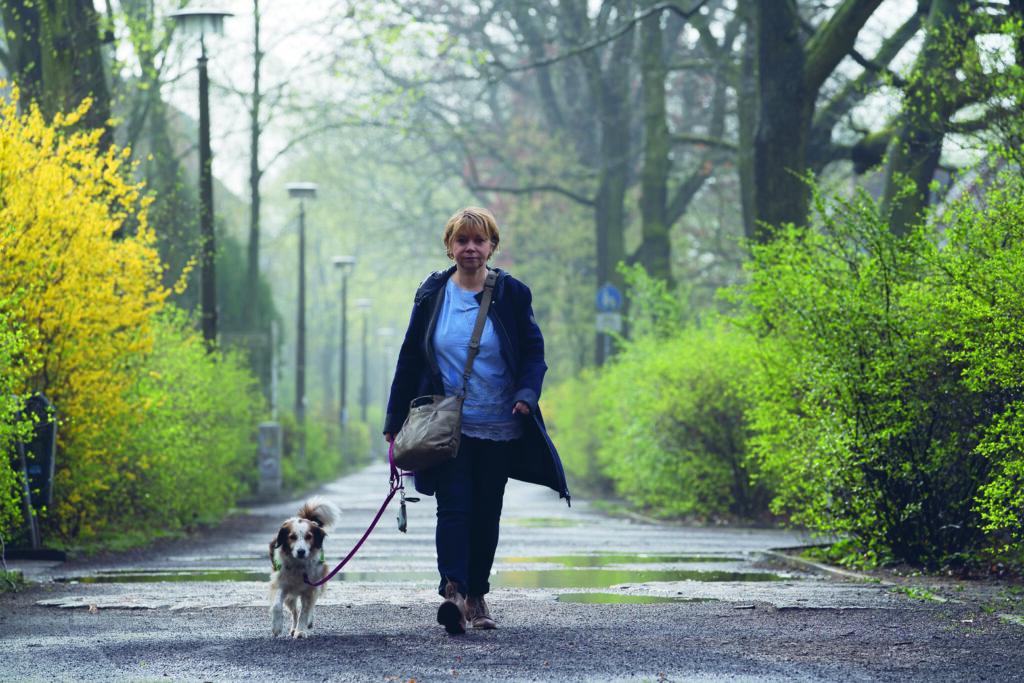 Eine Frau läuft über einen asphaltierten Waldweg auf die Kamera zu. Neben ihr läuft ein kleiner weiß-brauner Hund an der Leine.