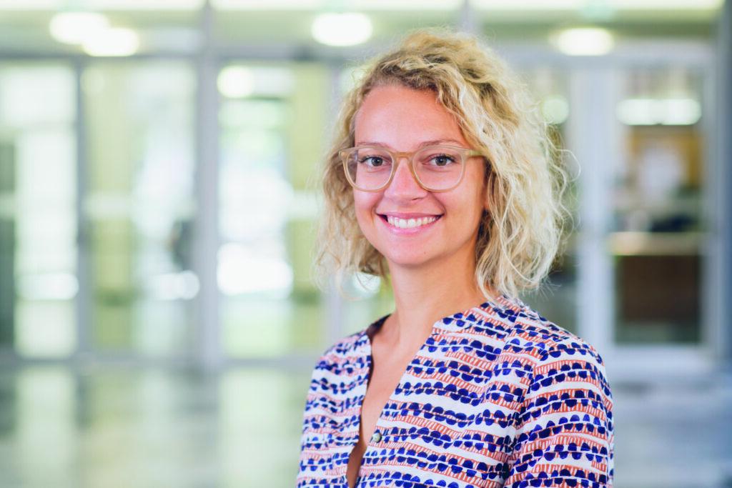 Eine Frau mit schulterlangen blonden, lockigen Haaren schaut lächelnd in die Kamera.
