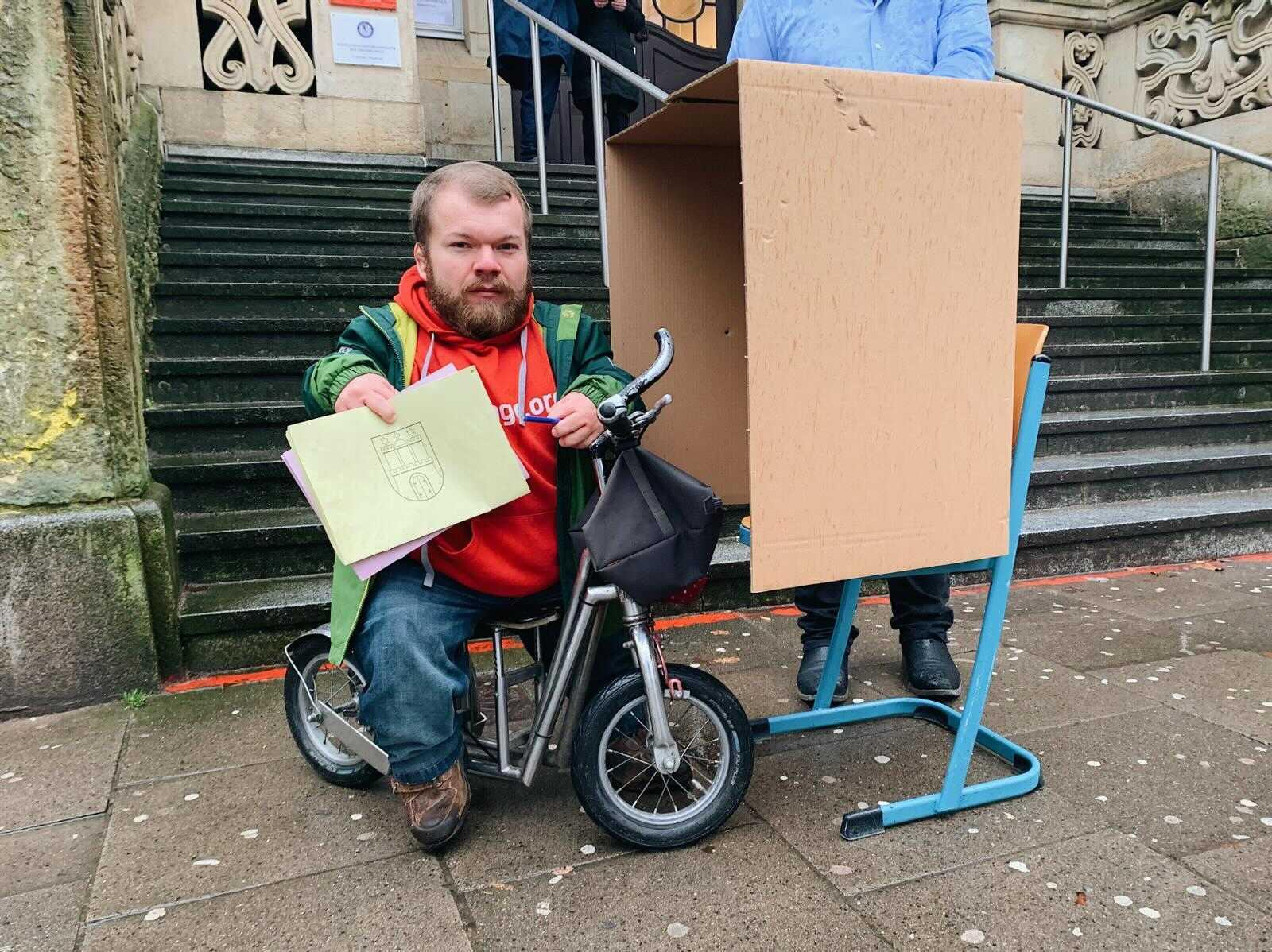 Ein kleinwüchsiger Mann sitzt vor einem Wahllokal, in das Treppen führen, auf seinem Dreirad. Vor ihm eine provisorische Wahlkabine.
