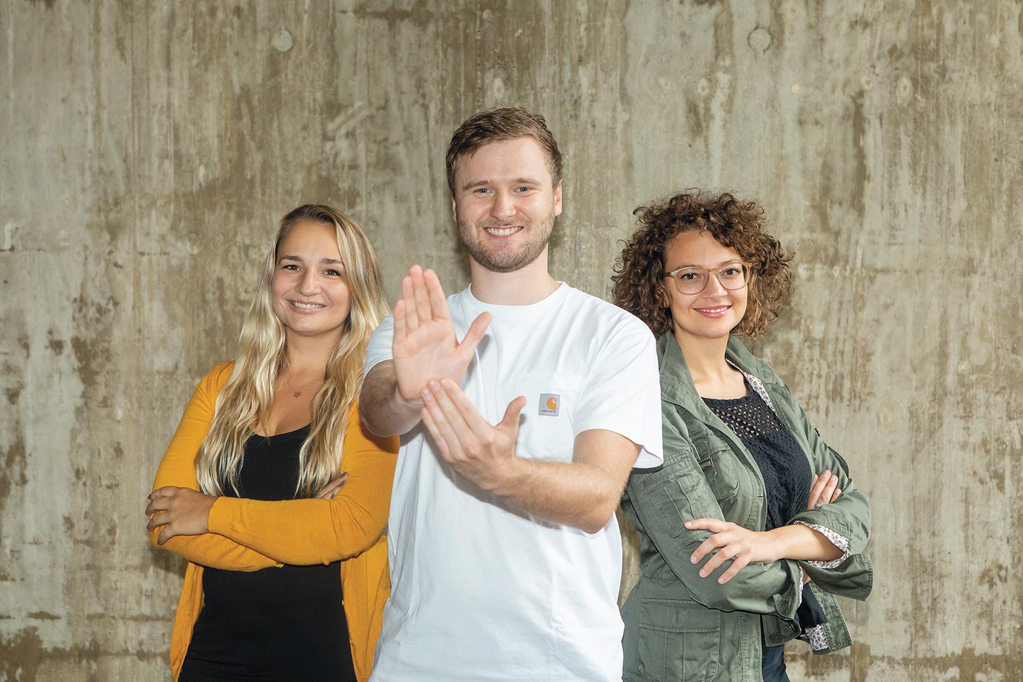 Gruppenfoto von zwei Frauen und einem Mann. Der Mann steht in der Mitte und streckt seine Handfläche der Kamera entgegen und berührt mit der anderen Hand diese. Es ist das Logo der Sendung Hand Drauf.