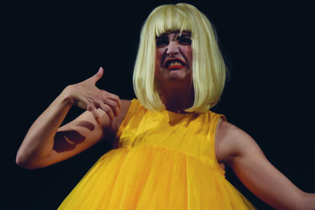 Eine weiße Frau trägt eine weiße Perrücke und ein gelbes Kleid. Sie schaut grimmig.