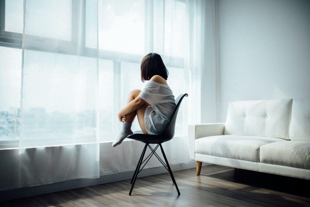Eine Person sitzt in einem Zimmer auf einem Stuhl und schaut aus dem Fenster.