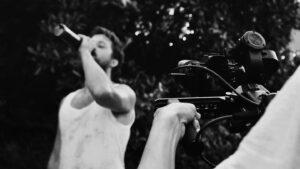 Ein Mann im weißen Unterhem wird von einer Person mit einer Kamera gefilmt. Es ist ein schwarz-weiß-Bild.