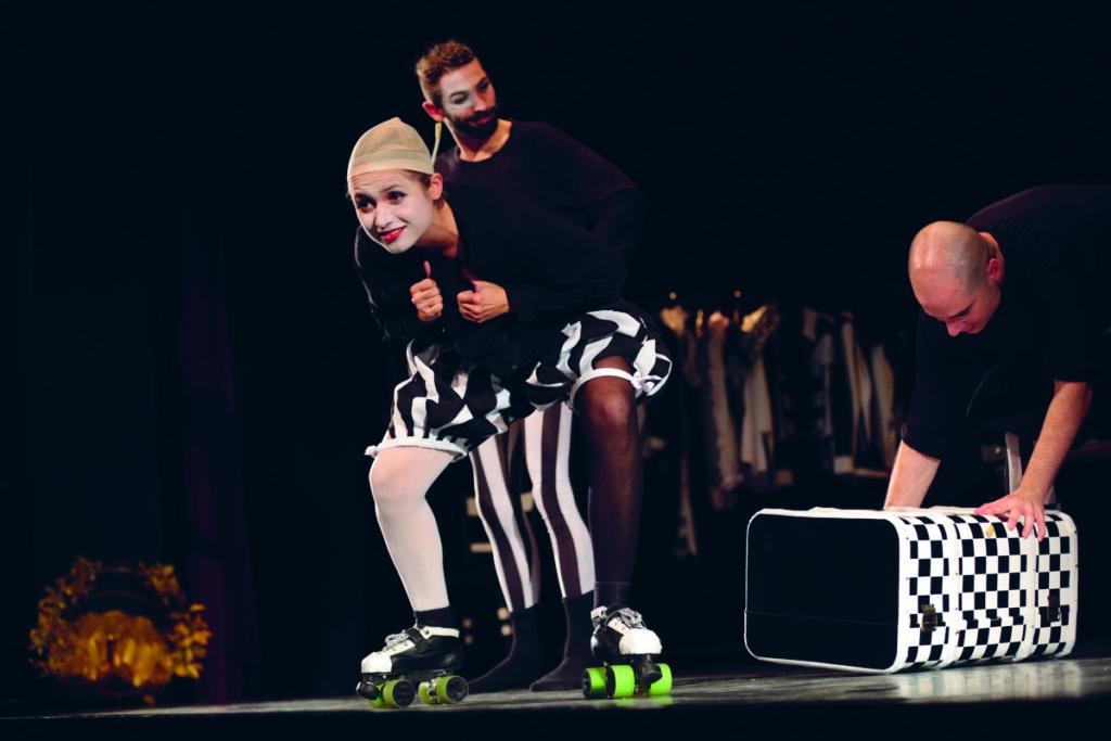 Eine weiße Frau performt auf einer Bühne. Sie trägt schwarz-weiß gemusterte Klamotten.