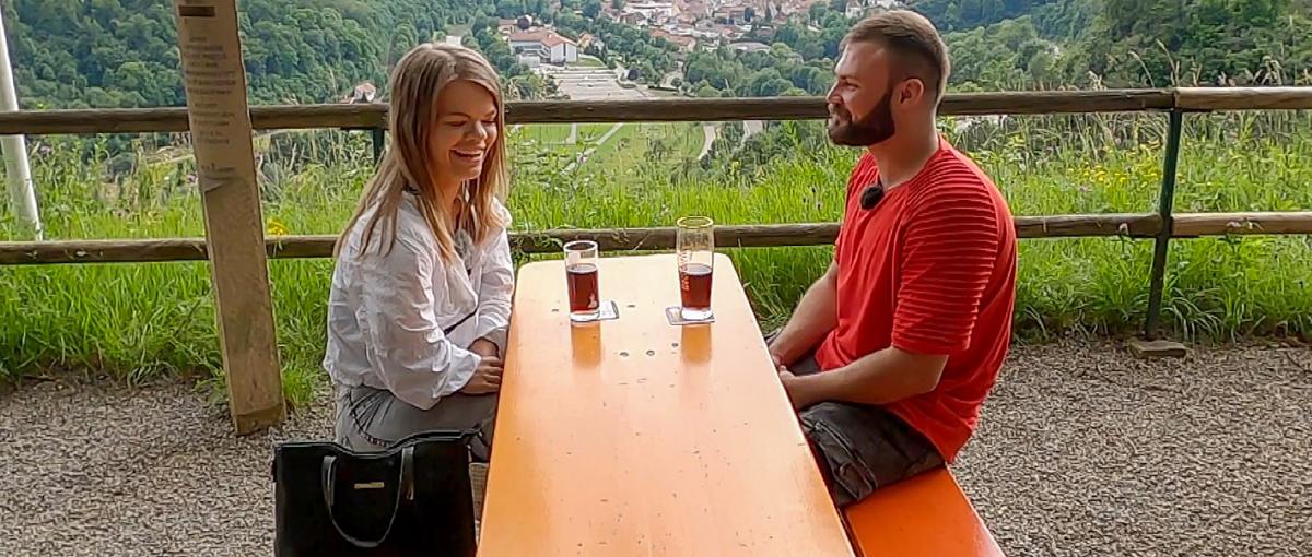 Eine kleinwüchsige Frau und ein Mann sitzen sich an einem Tisch gegenüber. Auf dem Tisch stehen getränke. Im Hintergrund der Ausblick auf ein Tal.