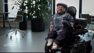 Foto von Raul Krauthausen. Er sitzt in einem Elektrorollstuhl in einem Büro und schaut in die Kamera.
