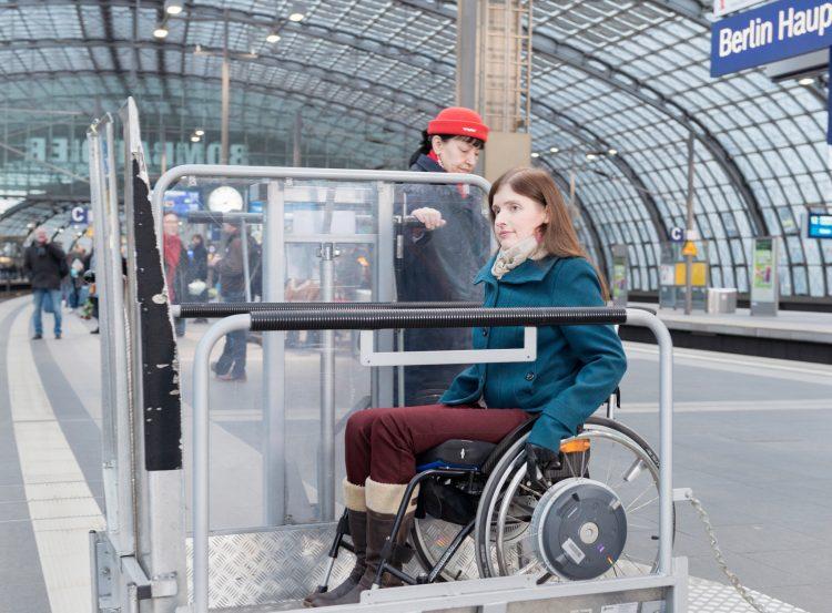 Eine Frau im Rollstuhl gelangt über eine Hebebühne in einen ICE
