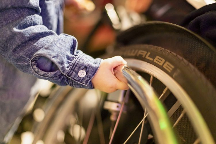 Eine Kinderhand greift an ein Rad eines Rollstuhls.