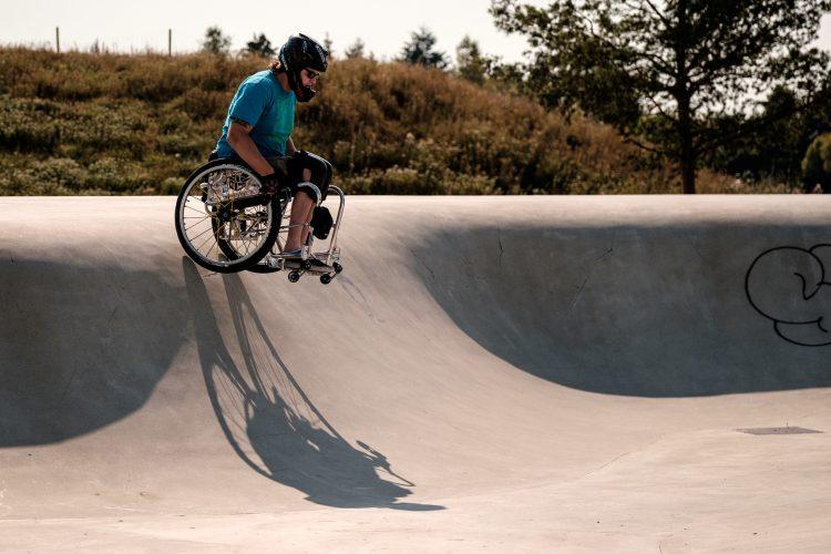Ein Rollstuhlfahrer mit Helm ist auf einer Bahn für Skater und fährt eine Rampe herab.