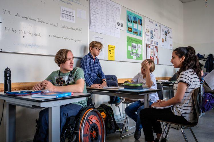 In einem Klassenzimmer reden vier Schüler+innen miteinander. Ein sSchüler sitzt im Rollstuhl.